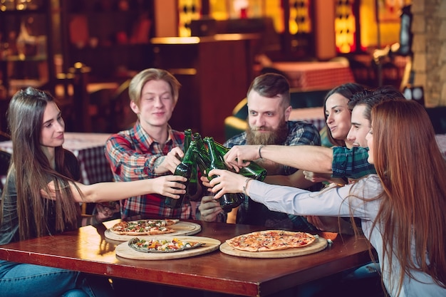 Amigos, tomar uma bebida em um bar, sentado em uma mesa de madeira com cervejas e pizza.