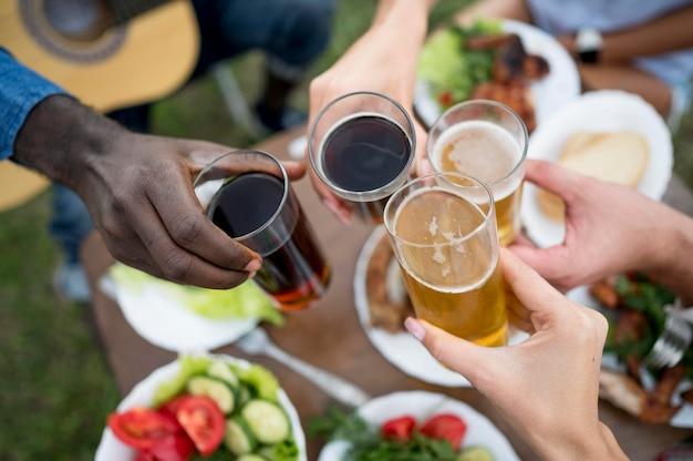Amigos torcendo com cerveja e refrigerante em um churrasco