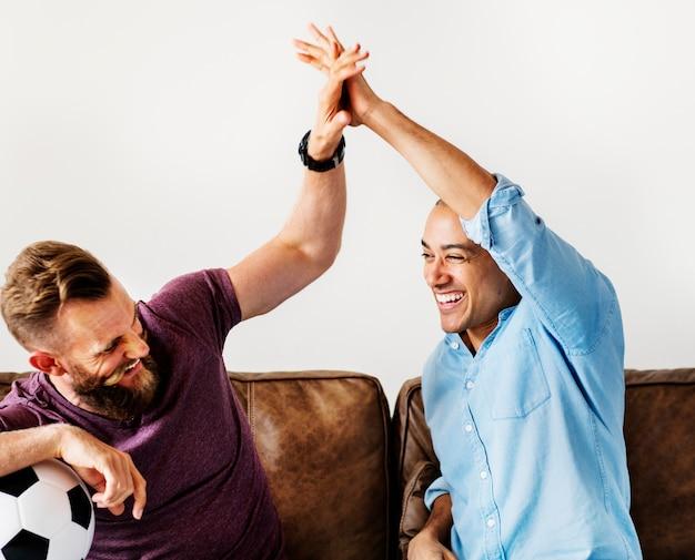 Amigos torcendo um jogo na televisão juntos