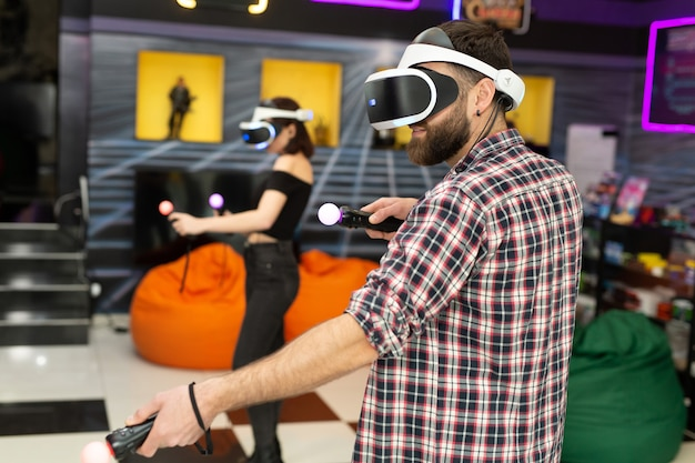 Amigos, um homem e uma mulher usam um fone de ouvido de realidade virtual com óculos e controladores de movimento de mão na área de jogo. imagem do conceito de tecnologias modernas.