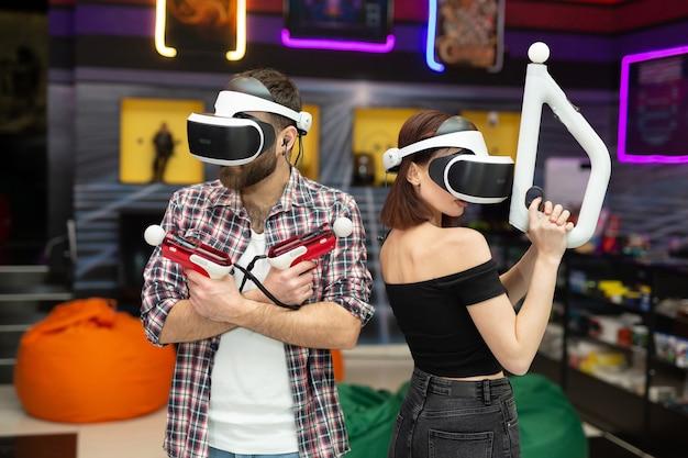 Amigos, um homem e uma mulher usam um fone de ouvido de realidade virtual com óculos e controles de movimento manual e armas na área de jogo.