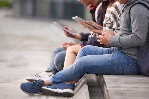 Amigos usando dispositivos ao ar livre