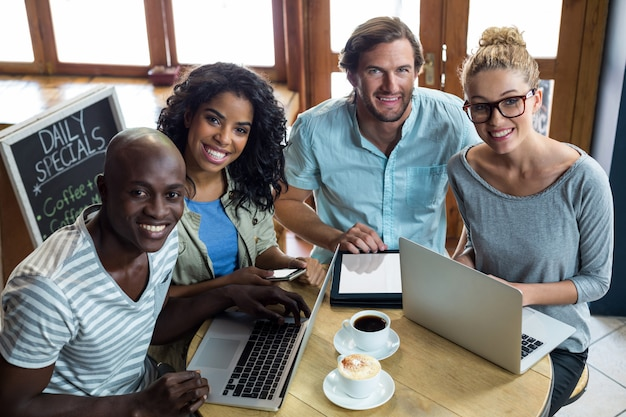 Amigos usando laptop e tablet digital enquanto tomando café no café