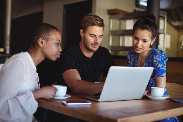 Amigos usando laptop enquanto tomam café