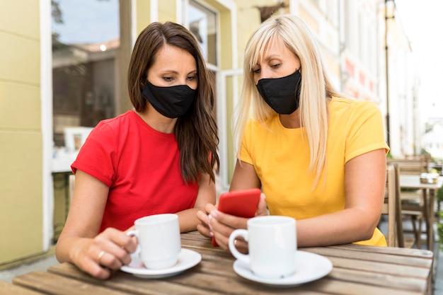 Amigos usando máscaras e apreciando a vista frontal do café