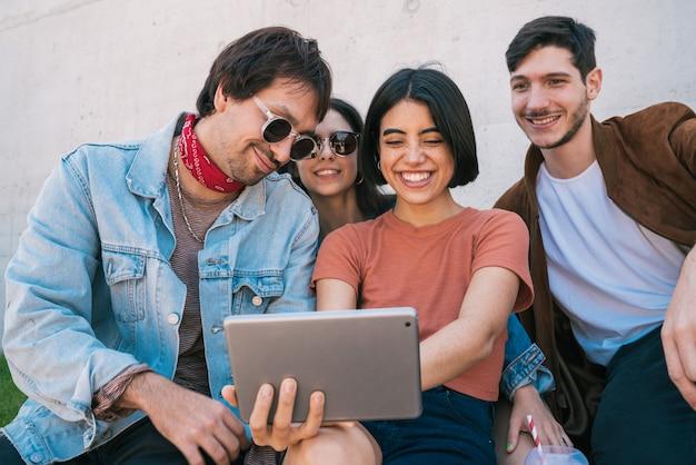 Amigos, usando o tablet digital juntos ao ar livre.