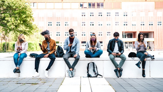 Amigos usando smartphone coberto por máscara na terceira onda da covid