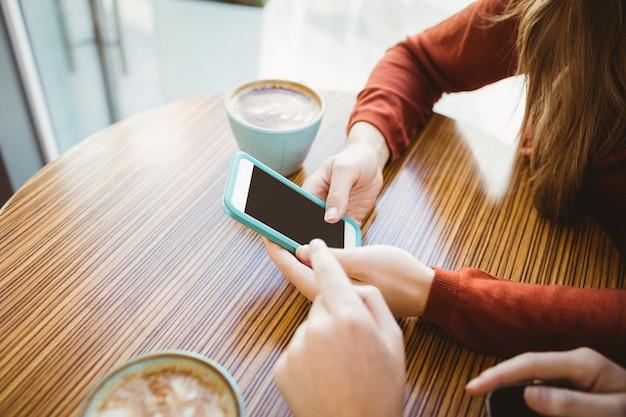 Amigos usando smartphone e tomando café em uma cafeteria