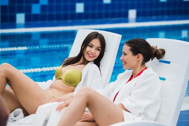 Amigos vestidos de roupão de banho e biquíni relaxando no spa ao lado da piscina