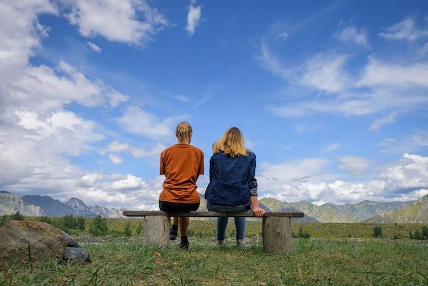 Amigos viajam e admiram a vista magnífica da cordilheira sob o céu azul em um dia ensolarado