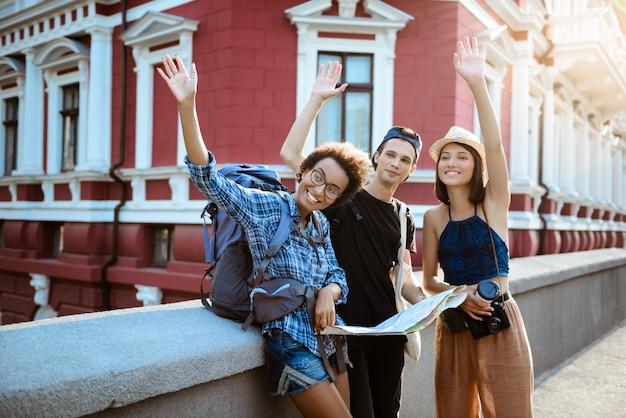 Amigos viajantes com mochilas sorrindo, cumprimentando, olhando a rota no mapa na rua.