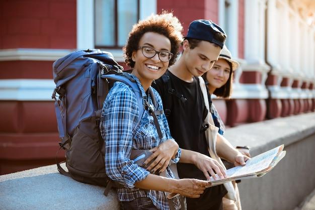 Amigos viajantes com mochilas sorrindo, olhando a rota no mapa na rua.