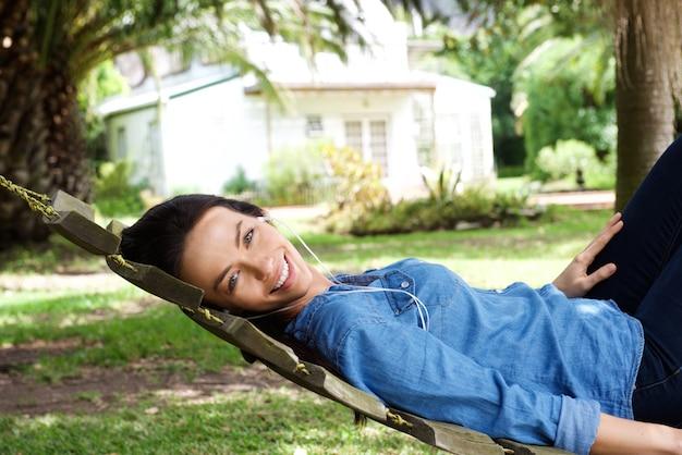 Amiling mulher relaxante fora ouvindo música