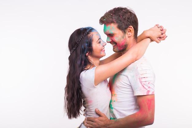 Amizade, amor, festival de holi, conceito de pessoas - jovem casal brincando com cores no festival de holi na superfície branca