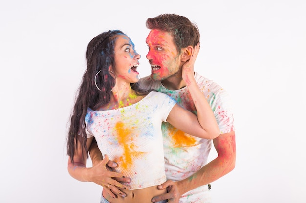 Amizade, amor, festival de holi, conceito de pessoas - jovem casal brincando com cores no