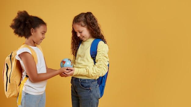 Amizade da escola de garotas segurando um espaço de cópia do globo terrestre