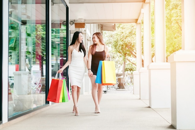 Amizade das mulheres felizes desfrutando gastos com sacolas de compras