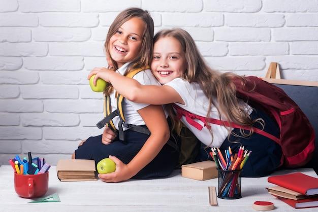 Amizade de pequenas irmãs em sala de aula no dia do conhecimento. amizade e relações familiares.