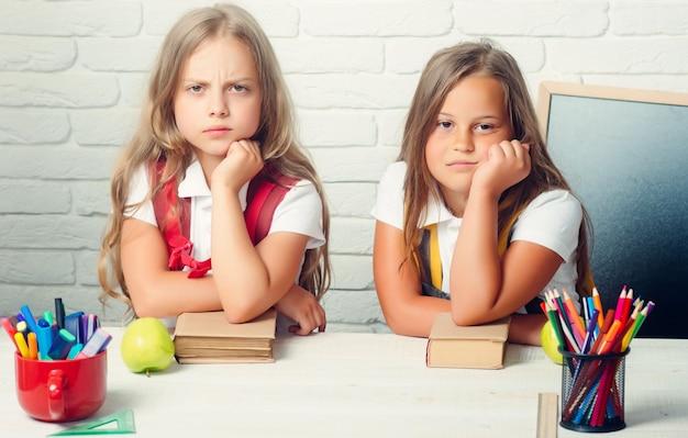Amizade de pequenas irmãs em sala de aula no dia do conhecimento. as meninas comem maçã na hora do almoço.
