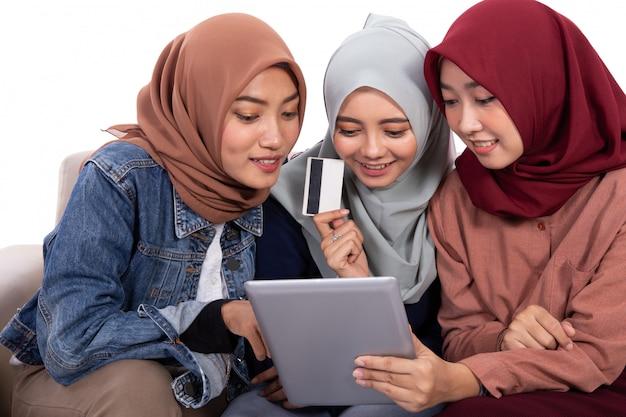 Amizade de três mulheres com véu enquanto relaxa sentado e segurando o cartão de crédito para comprar em uma loja online