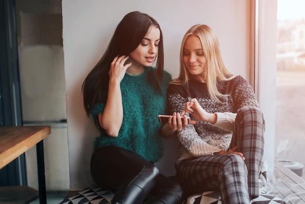 Amizade e tecnologia. duas garotas bonitas usando smartphones enquanto bebem chá ou café em um café