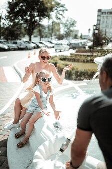 Amizade em família. mulher bonita se divertindo com sua filha sentada com eles perto da fonte.