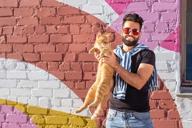 Amizade entre homem e gato no fundo da parede colorida ao ar livre.