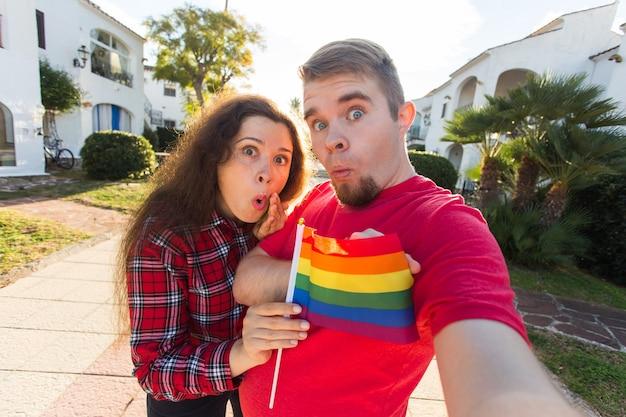 Amizade gay e lésbica segurando a bandeira do arco-íris