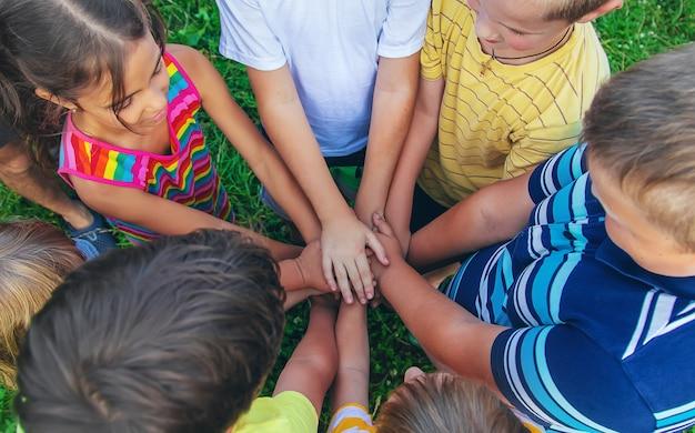 Amizade infantil, mãos de crianças na rua. foco seletivo. miúdo. Foto Premium