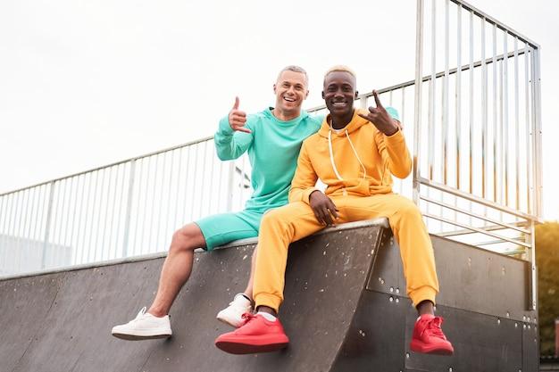 Amizade multiétnica. amigos negros afro-americanos e caucasianos passando um tempo juntos na pista de skate