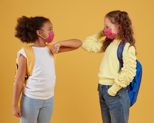 Amizade na escola de garotas usando máscara médica