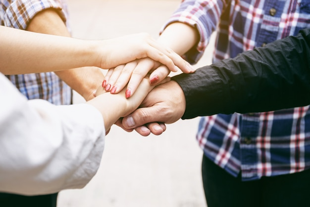 Amizade pessoas parceria trabalho em equipe empilhando as mãos no fundo branco conceito de trabalho em equipe de negócios