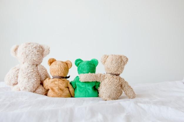 Amizade - quatro ursos de pelúcia segurando em seus braços