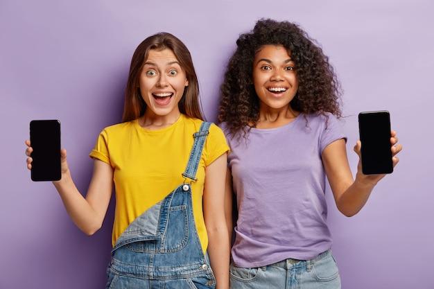 Amizade, tecnologia, conceito de publicidade. dois adolescentes multiétnicos sorridentes se aproximam, mostram smartphones com telas de maquete para seu texto