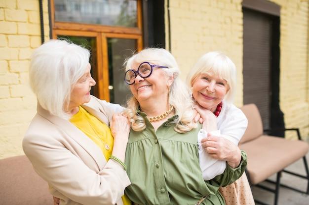 Amizade. três senhoras suaves parecendo felizes em um tempo de namoro