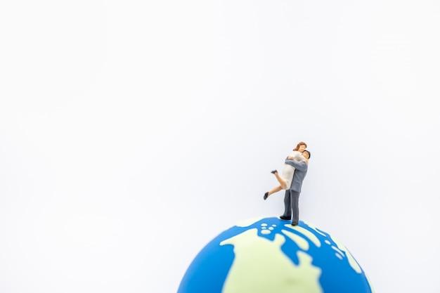 Amn e mulher miniatura figura abraço e pé na mini bola do mundo.