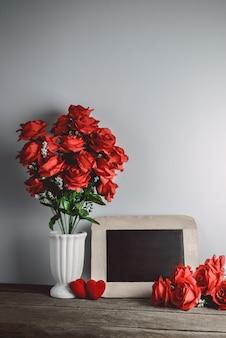 Amo a forma de corações, rosas vermelhas e placa de giz vazia no fundo de madeira