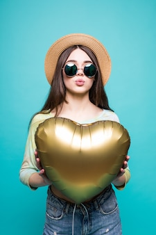 Amo a mulher sorrindo segurando um balão em forma de coração de ouro. linda linda jovem apaixonada isolada no verde