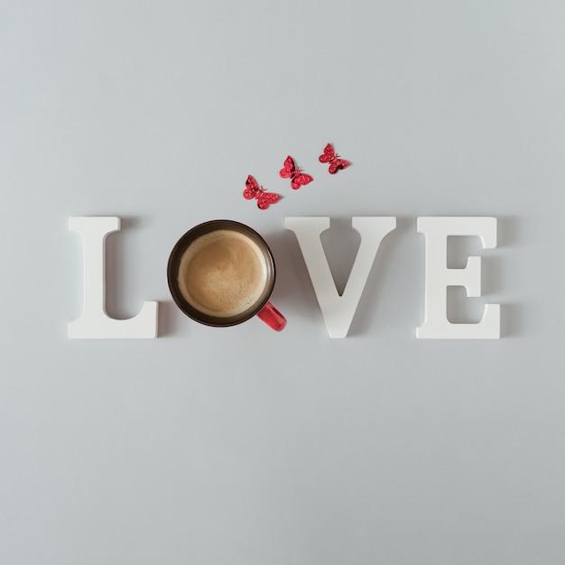 Amo a palavra com uma xícara de café e borboletas na mesa cinza.