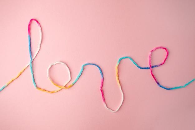 Amo a palavra escrita com letras de fio de lã, conceito e plano de fundo para o dia dos namorados