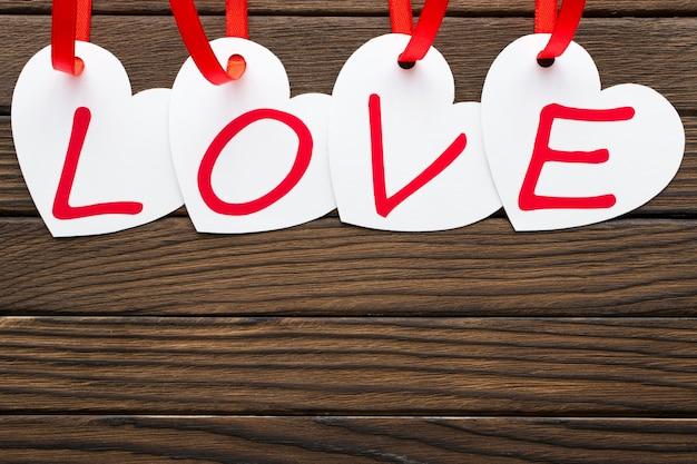 Amo a palavra escrita em cartões em forma de coração brancos no fundo de madeira.