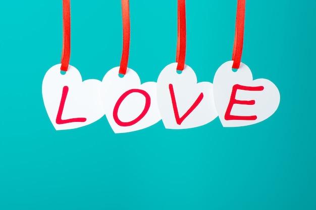 Amo a palavra escrita em cartões em forma de coração brancos sobre o fundo turquesa.
