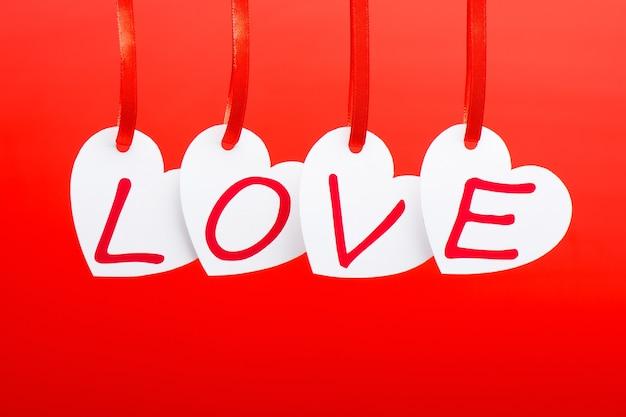 Amo a palavra escrita em cartões em forma de coração brancos sobre o fundo vermelho.