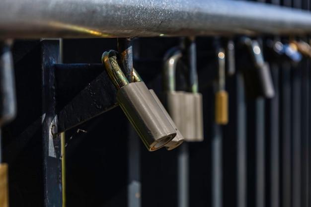 Amo cadeados pendurados no trilho entre outros cadeados variegados