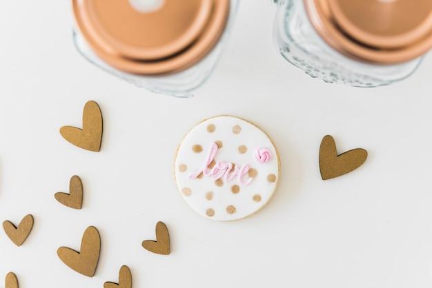 Amo circular biscoito com formas de coração e jar em pano de fundo branco