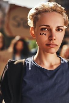 Amo, close-up de uma jovem loira com a palavra amor escrita em seu rosto