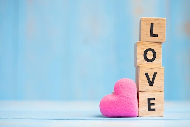 Amo cubos de madeira com decoração de forma de coração rosa em fundo de mesa azul
