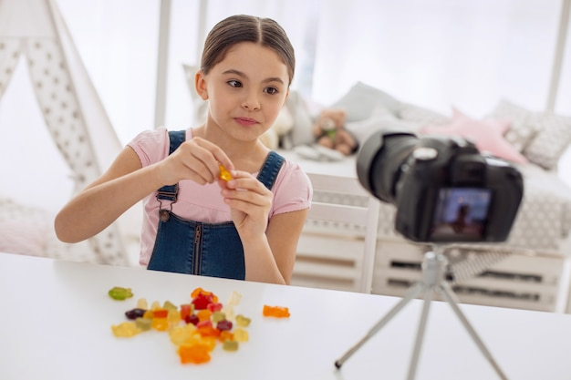 Amo doces. garota pré-adolescente simpática e otimista sentada à mesa em frente a uma pilha de ursinhos de goma e provando-os enquanto grava para seu videoblog