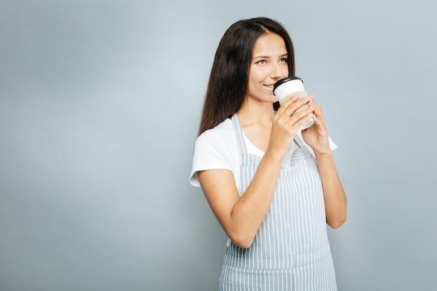 Amo esse cheiro. morena positiva expressando positividade enquanto bebe cappuccino e olha para cima, isolada em cinza