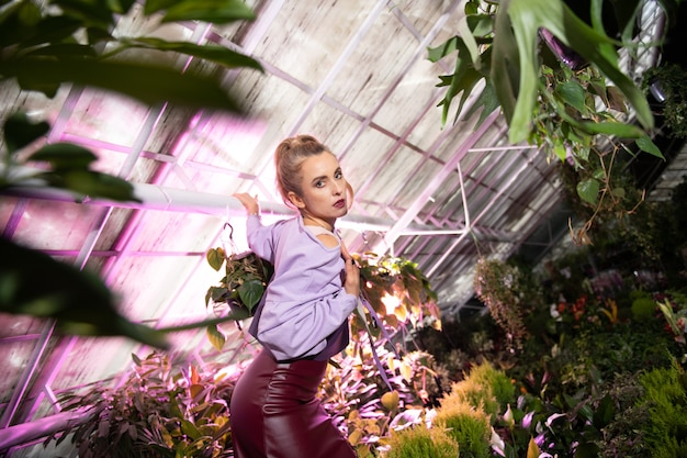 Amo flores. mulher agradável e bonita virando o rosto para você enquanto está no jardim de flores